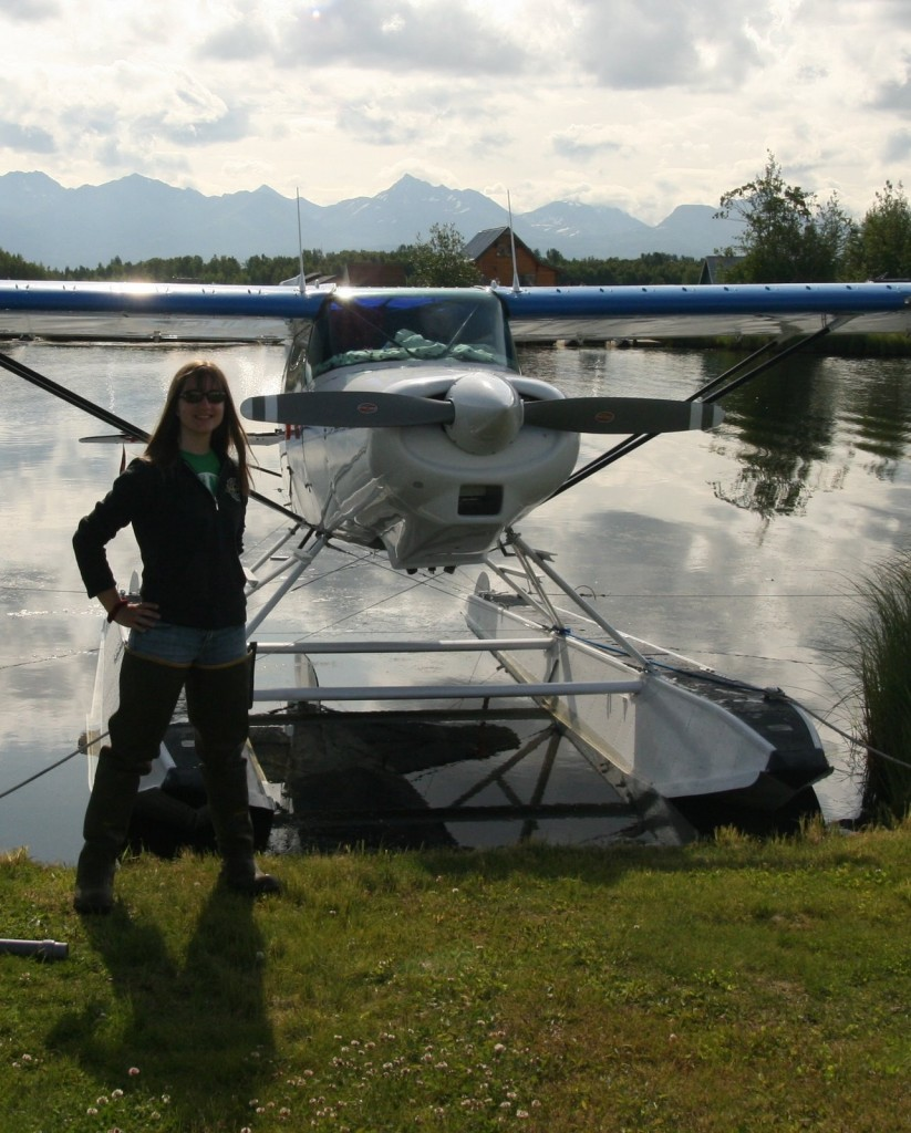 """Sporting the latest fashion in hip waders - Rachel stands in front of Scott's float plane. It is lovingly referred to as """"the baby."""""""